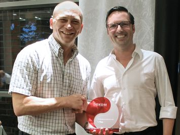 DEKOM CEO Jörg Weisflog with Prysm award